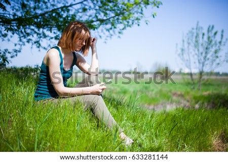 young woman make photo on cellphone, spring flowers background