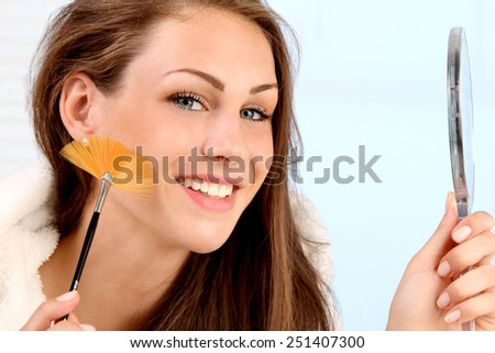 young woman makeup her face - stock photo