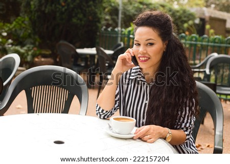young woman making a phone call at a coffee shop. - stock photo