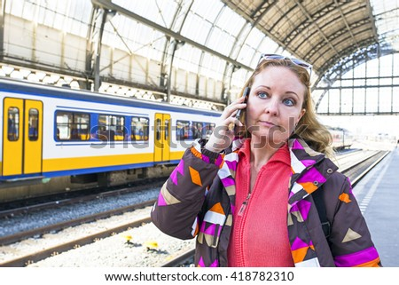 Young woman making a phone call at the central station in Amsterdam the Netherlands - stock photo
