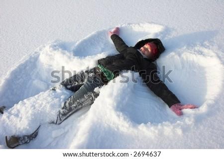Young woman making a snowangel - stock photo