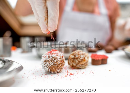 Young woman making and decorating chocolate candy with coconade, red sugar and almonds on the white table - stock photo