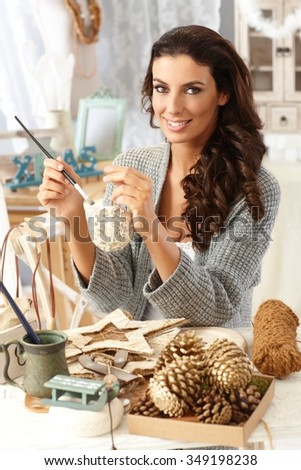Young woman making christmas decoration at home, painting ornaments, sitting at table, smiling, looking at camera at vintage home.