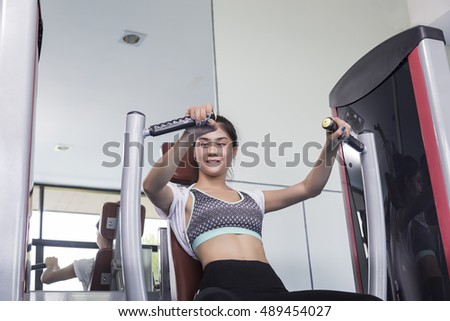 Young woman making exercise happily fun at the gym