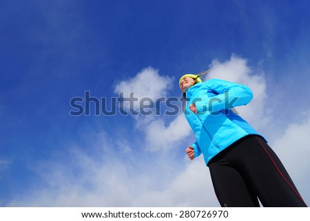 Young woman making exercises on a snow field - stock photo