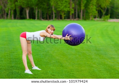 Young woman making fitness exercises in th park. - stock photo