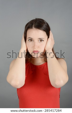 Young woman making hand gestures, hear no evil - stock photo