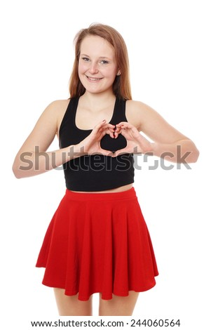 young woman making heart shape with her hands - stock photo