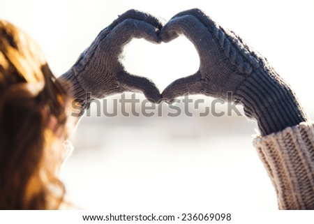 Young woman making heart symbol with hands, wintertime - stock photo