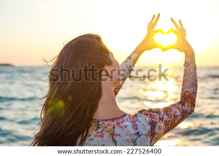 young woman making heart with her hands round the sun in sunset - stock photo