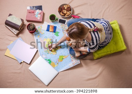 Young woman making marks on the map while sitting on the floor, view from above. Trip planning concept. - stock photo