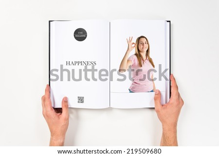Young woman making Ok sign printed on book - stock photo