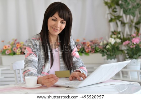 young woman making purchases on the internet while sitting at the table