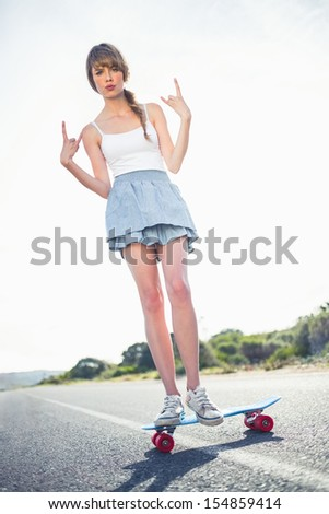 Young woman making rock and roll gesture while balancing on her skateboard on a deserted road - stock photo