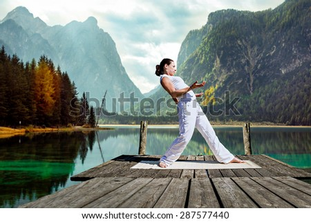 young woman making tai chi exercise at a lake - stock photo