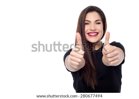 Young woman making thumb up gesture by two hands - stock photo