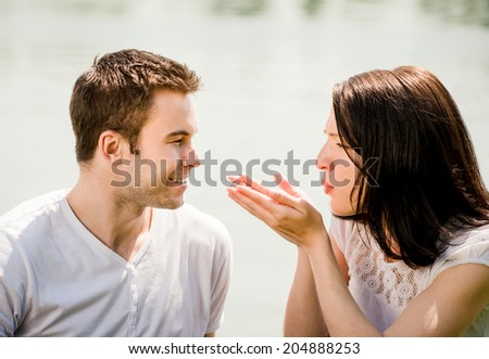 Young woman man blowing to hands, happy man is standing against