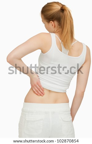 Young woman massaging her back against white background - stock photo