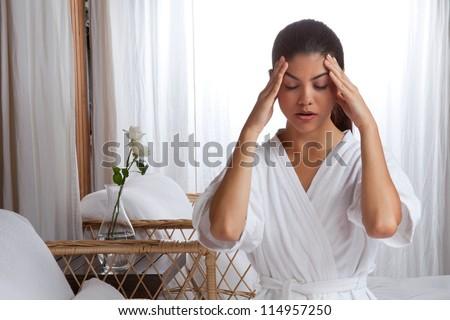 Young woman massaging her face wearing bathrobe. - stock photo