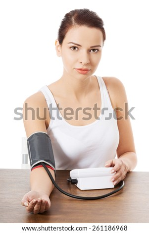 Young woman measuring blood pressure. - stock photo