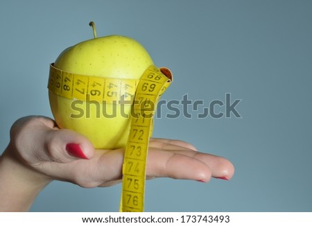 Young woman measuring body and holding apple