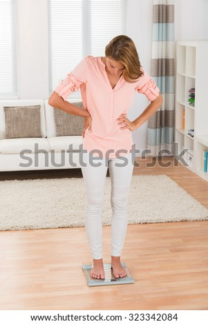 Young Woman Measuring Body Weight On Weighing Scale At Home - stock photo