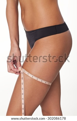 Young woman measuring her thigh with a inch tape measure - stock photo