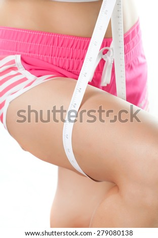 Young woman measuring her thigh with measuring tape, Beauty body care and diet - stock photo