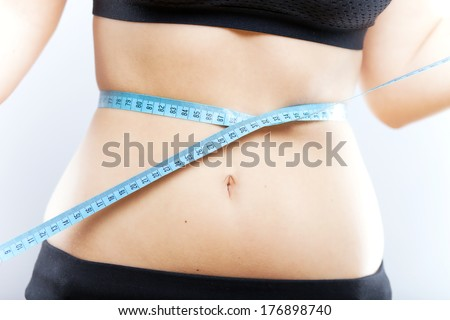 Young woman measuring her waist after exercise