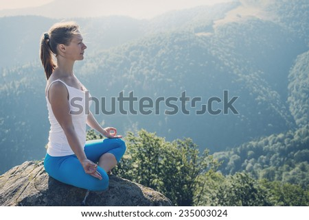 Young woman meditate on the top of mountain - stock photo