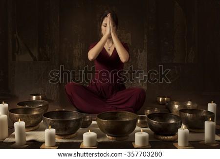 Young woman meditates before playing on Tibetan singing bowls - stock photo