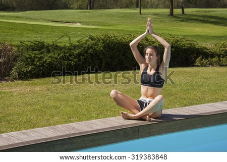Young woman meditating at the side of a pool sitting cross legged in the lotus position with her eyes closed and serene expression, garden backdrop - stock photo