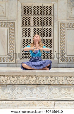 Young woman meditating at the wall of Taj Mahal. Agra, India - stock photo