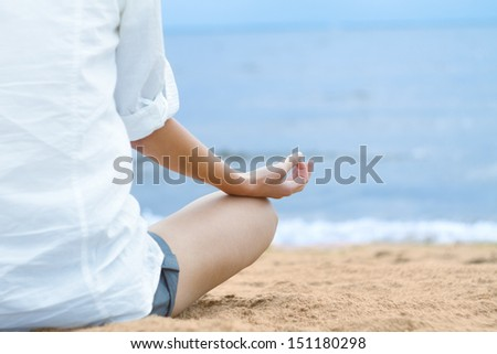 Young woman meditating in lotus position while sitting on beach