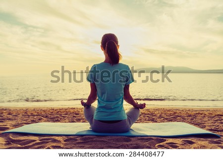 Young woman meditating in pose of lotus on beach near the sea at sunset in summer, rear view