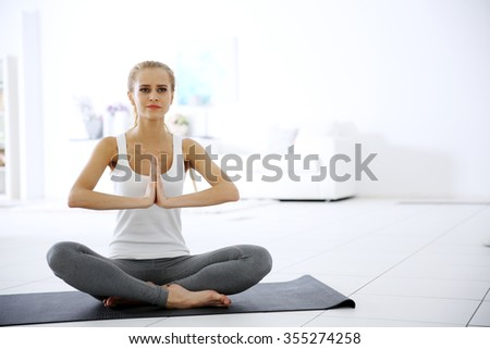 Young woman meditating in the room - stock photo