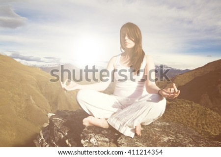 Young woman meditating in the wilderness with beautiful mountain range as a background. - stock photo