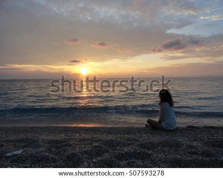 young woman meditating on a greek beach at sunset