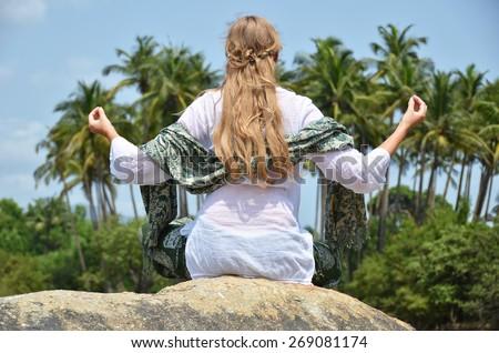 Young woman meditating on Agonda beach. Goa, India - stock photo