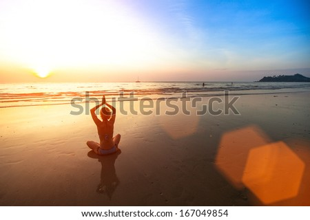 Young woman meditating on the beach at sunset. - stock photo