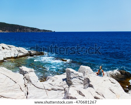 Young woman meditating on the cliff against sea and blue sky.