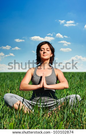 young woman meditating on the field at sunny day - stock photo