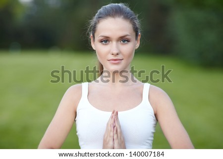 Young woman meditating or praying, outdoor - stock photo