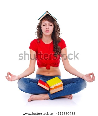 Young woman meditating with colorful books, white background - stock photo