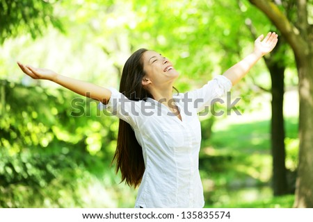 Young woman meditating with open arms standing in fresh spring greenery with her head raised to the sky and her eyes closed rejoicing in the freshness and new beginnings of spring and nature - stock photo