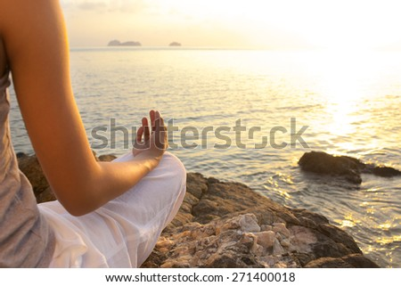 young woman meditation in a yoga pose on the tropical beach - stock photo