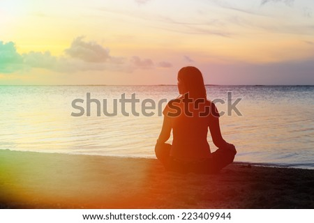 young woman meditation on sunset beach - stock photo