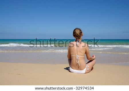 Young woman meditation on the beach. Fuerteventura, Canary Islands, Spain