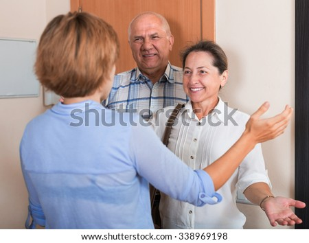 Young woman meeting mature friends - stock photo