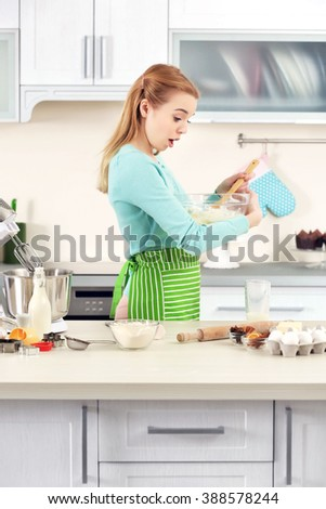 Young woman mixing dough in a bowl